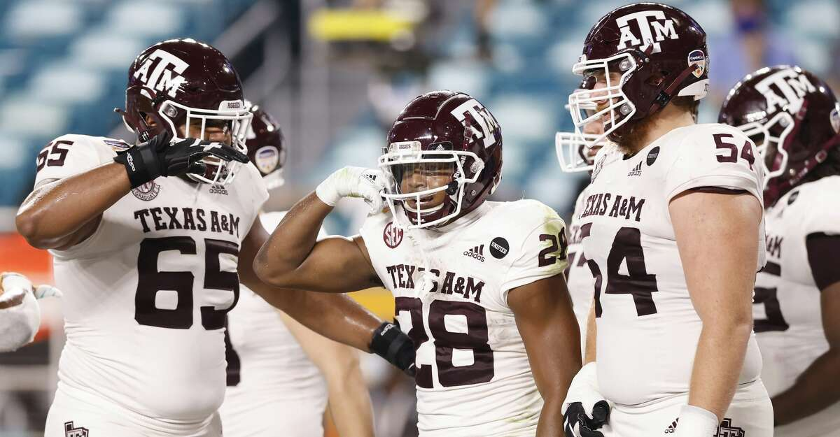 Isaiah Spiller #28 of the Texas A&M Aggies celebrates with his teammates after rushing for a nine-yard touchdown against the North Carolina Tar Heels during the first half of the Capital One Orange Bowl at Hard Rock Stadium on January 02, 2021 in Miami Gardens, Florida. (Photo by Michael Reaves/Getty Images)