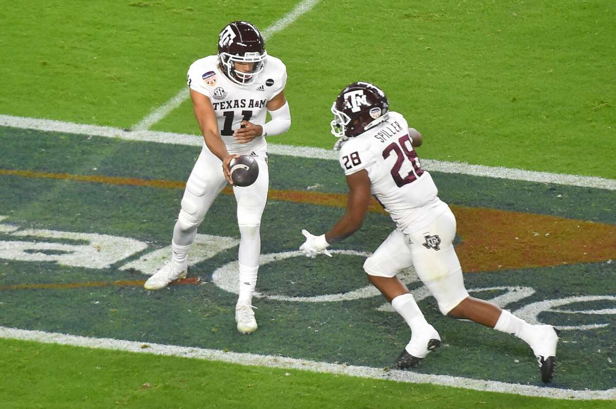 MIAMI GARDENS, FL - JANUARY 02: Kellen Mond #11 of the Texas A&M Aggies hands off to Isaiah Spiller #28 during the first quarter of the Capital One Orange Bowl against the North Carolina Tar Heels at Hard Rock Stadium on January 2, 2021 in Miami Gardens, Florida. (Photo by Eric Espada/Getty Images)