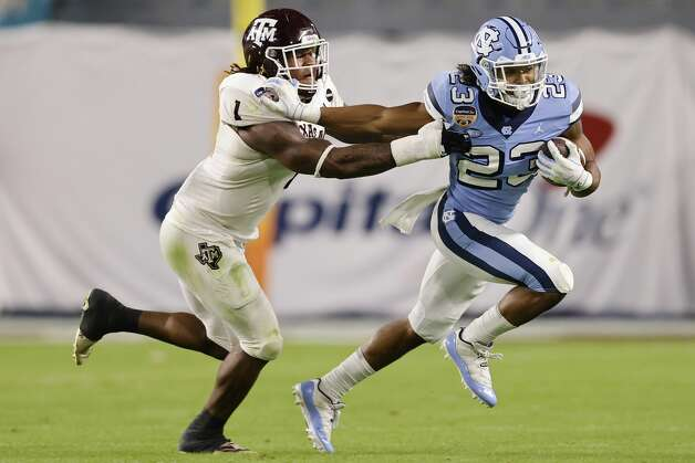 MIAMI GARDENS, FLORIDA - JANUARY 02: Josh Henderson #23 of the North Carolina Tar Heels stiff arms Buddy Johnson #1 of the Texas A&M Aggies during the first half of the Capital One Orange Bowl at Hard Rock Stadium on January 02, 2021 in Miami Gardens, Florida. (Photo by Michael Reaves/Getty Images) Photo: Michael Reaves/Getty Images / 2021 Getty Images