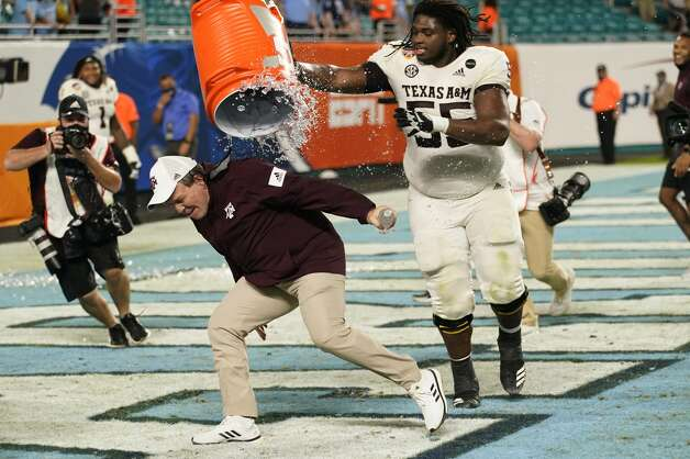 Texas A&M offensive lineman Kenyon Green (55) douses head coach Jimbo Fisher at the end of the Orange Bowl NCAA college football game, Saturday, Jan. 2, 2021, in Miami Gardens, Fla. Texas A&M defeated North Carolina 41-27. (AP Photo/Lynne Sladky) Photo: Lynne Sladky/Associated Press / AP