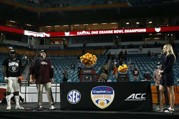 MIAMI GARDENS, FLORIDA - JANUARY 02: Devon Achane #6, head coach Jimbo Fisher of the Texas A&M Aggies talk with ESPN reporter Katie George after defeating the North Carolina Tar Heels 41-27 in the Capital One Orange Bowl at Hard Rock Stadium on January 02, 2021 in Miami Gardens, Florida. (Photo by Michael Reaves/Getty Images) Photo: Michael Reaves/Getty Images / 2021 Getty Images