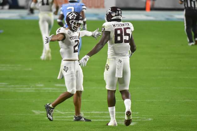 MIAMI GARDENS, FL - JANUARY 02: Chase Lane #2 of the Texas A&M Aggies celebrates with Jalen Wydermyer #85 after the offense scored a touchdown during the fourth quarter of the Capital One Orange Bowl against the North Carolina Tar Heels at Hard Rock Stadium on January 2, 2021 in Miami Gardens, Florida. (Photo by Eric Espada/Getty Images) Photo: Eric Espada/Getty Images / 2021 Getty Images