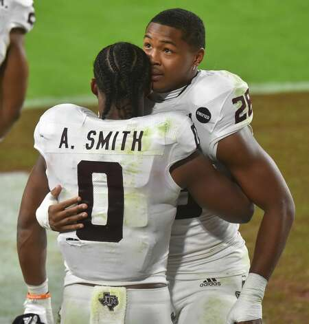 MIAMI GARDENS, FL - JANUARY 02: Ainias Smith #0 of the Texas A&M Aggies hugs Isaiah Spiller #28 after defeating the North Carolina Tar Heels 41-27 in the Capital One Orange Bowl at Hard Rock Stadium on January 2, 2021 in Miami Gardens, Florida. (Photo by Eric Espada/Getty Images) Photo: Eric Espada/Getty Images / 2021 Getty Images