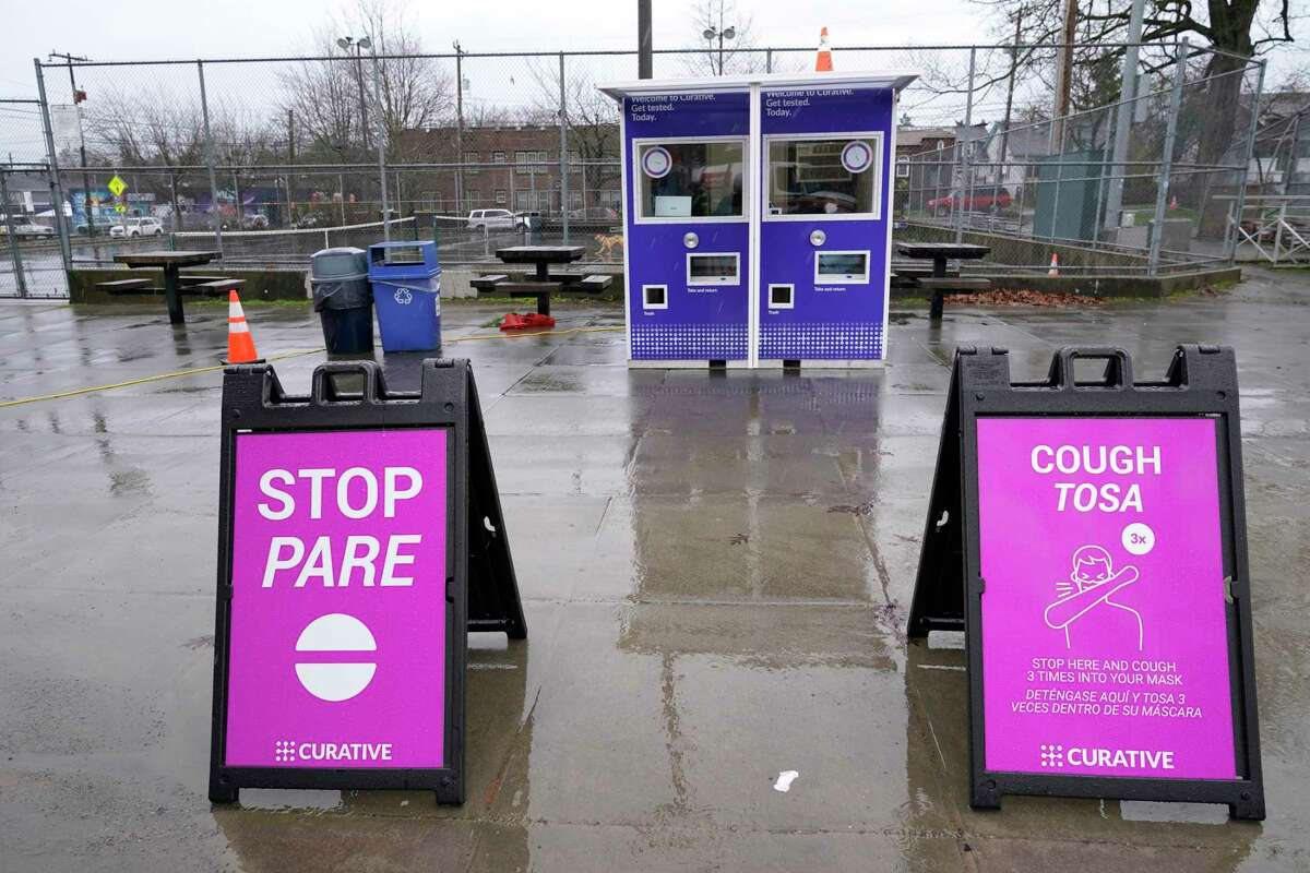 Signs give instructions to people approaching a walk-up kiosk testing site for COVID-19, Saturday, Jan. 2, 2021, at the Garfield Community Center in Seattle. The site is one of two kiosks that test using an oral swab and are operated by the city in partnership with the medical testing company Curative, which opened in December to supplement the city's larger drive-up testing locations that use nasal swabs.