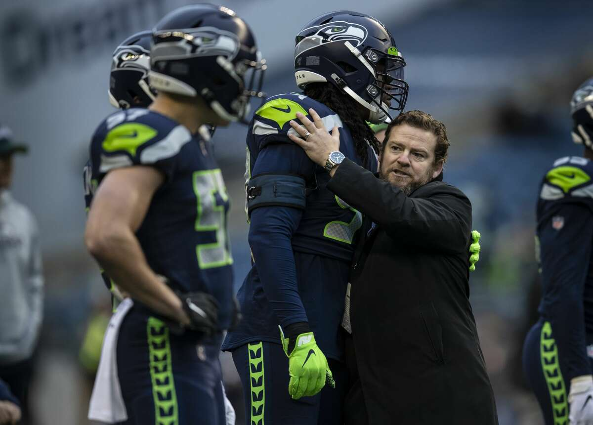 SEATTLE, WA - DECEMBER 22: Seattle Seahawks general manager John Schneider (R) gives defensive end Ziggy Ansah #94 of the Seattle Seahawks a hug before game against the Arizona Cardinals at CenturyLink Field on December 22, 2019 in Seattle, Washington. The Cardinals won 27-13. (Photo by Stephen Brashear/Getty Images)