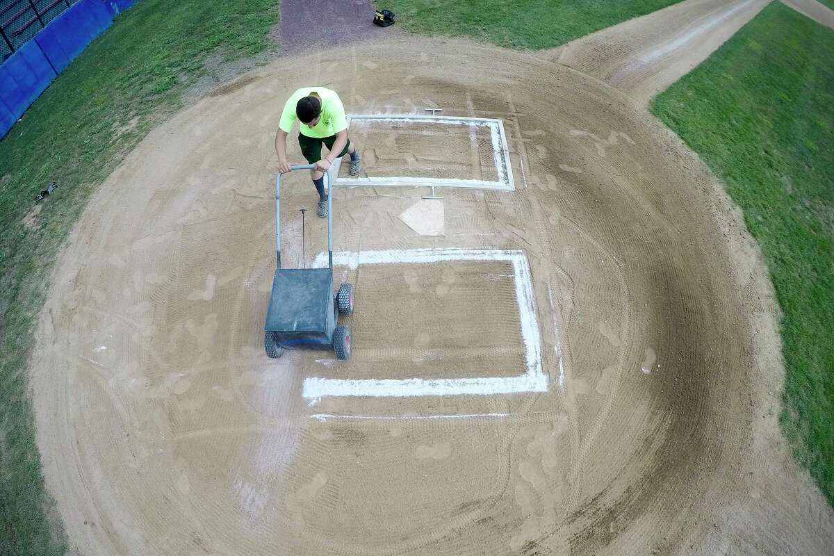 Mike Pinto, an employee with the City of Stamford Parks and Recreation Department layouts and stripes the batters box at Cubeta Stadium in preparation for games on July 28, 2020 in the Stamford Babe Ruth Baseball League in Stamford, Connecticut.