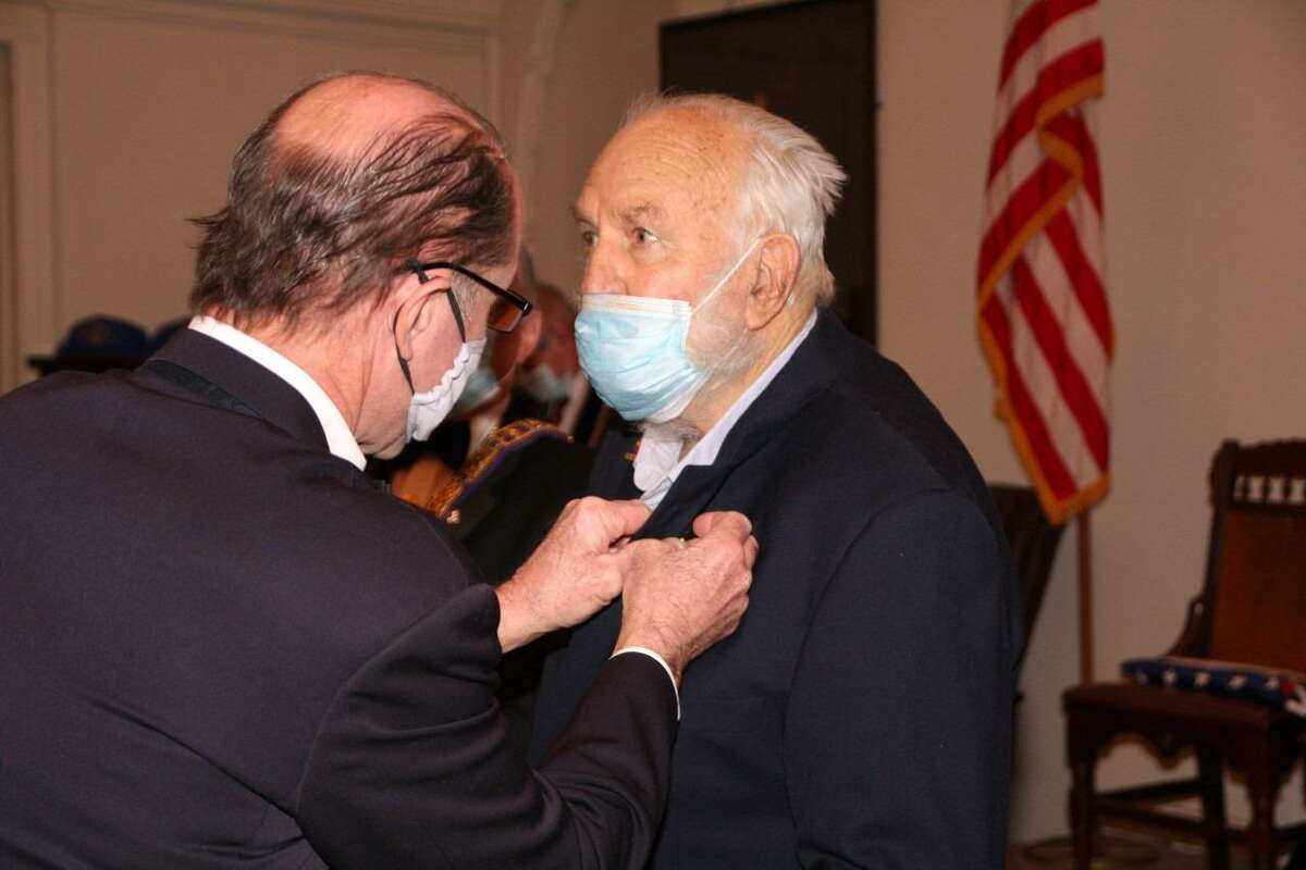 RW Bro. Bill Deickler secures the 50-year pin on Bro. Willard Carter's lapel.