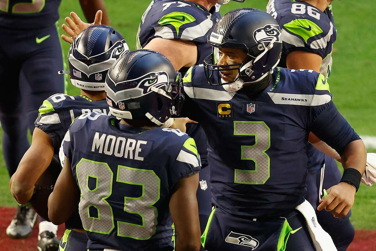 GLENDALE, ARIZONA - JANUARY 03: Quarterback Russell Wilson #3 of the Seattle Seahawks celebrates with wide receiver Tyler Lockett #16 after throwing a 6-yard touchdown reception during the second half of the NFL game against the San Francisco 49ers at State Farm Stadium on January 03, 2021 in Glendale, Arizona. (Photo by Christian Petersen/Getty Images)