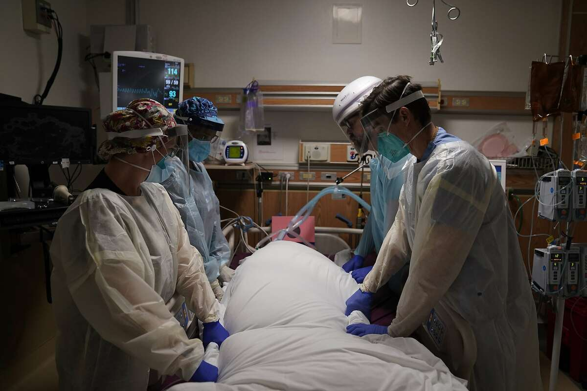 A medical team treats a COVID-19 patient last month at Providence Holy Cross Medical Center in Los Angeles.