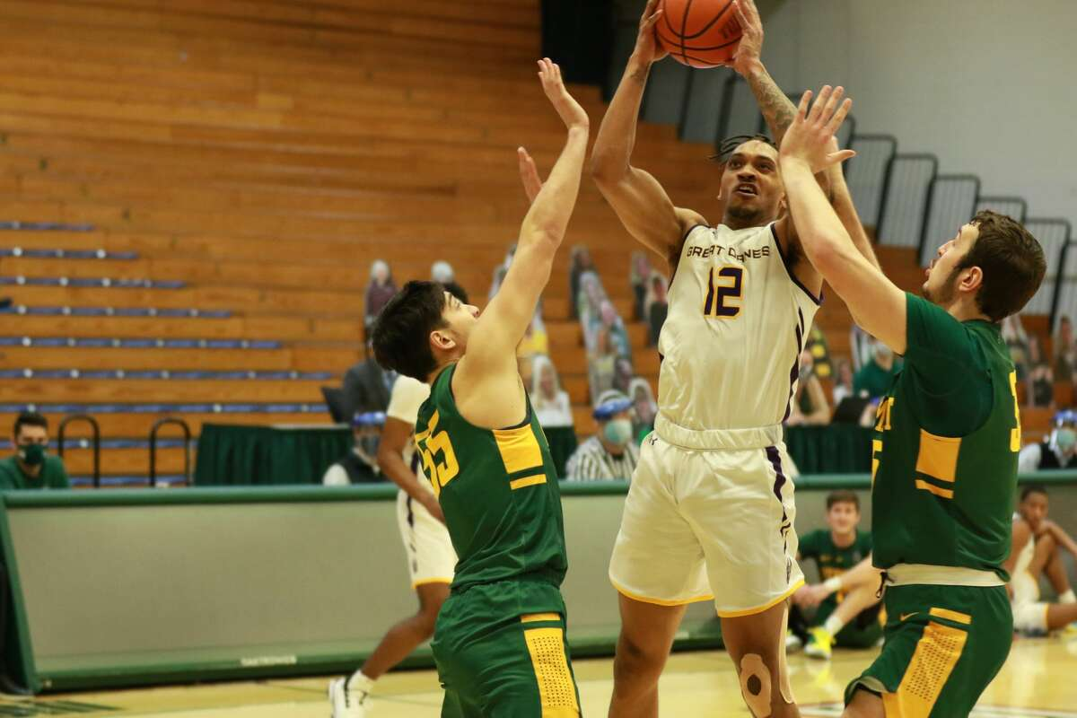 UAlbany's Kellon Taylor (12) tries to split Vermont defenders Robin Duncan, left, and Ryan Davis in an America East basketball game Sunday, Jan. 3, 2021, at Patrick Gymnasium in Burlington, Vt. (Nich Hall/UVM athletics)