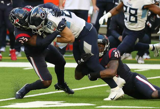 Tennessee Titans tight end Anthony Firkser (86) makes a first down reception as he is hit by Houston Texans safety A.J. Moore (33) and inside linebacker Zach Cunningham (41) during the first half of an NFL football game at NRG Stadium on Sunday, Jan. 3, 2021, in Houston. Photo: Brett Coomer/Staff Photographer / © 2021 Houston Chronicle