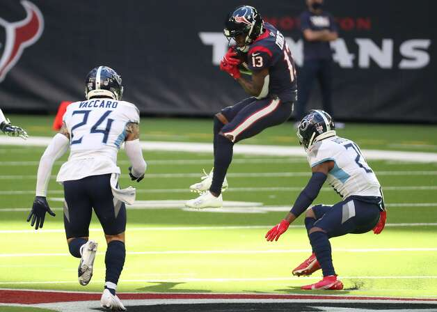 Houston Texans wide receiver Brandin Cooks (13) leaps to make a catch against Tennessee Titans strong safety Kenny Vaccaro (24) and cornerback Malcolm Butler (21) during the first half of an NFL football game at NRG Stadium on Sunday, Jan. 3, 2021, in Houston. Photo: Brett Coomer/Staff Photographer / © 2021 Houston Chronicle
