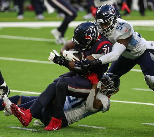 Houston Texans running back David Johnson (31) is stopped by Tennessee Titans inside linebacker Rashaan Evans (54) and free safety Kevin Byard (31) during the third quarter of an NFL football game at NRG Stadium on Sunday, Jan. 3, 2021, in Houston. Photo: Brett Coomer/Staff Photographer / © 2021 Houston Chronicle