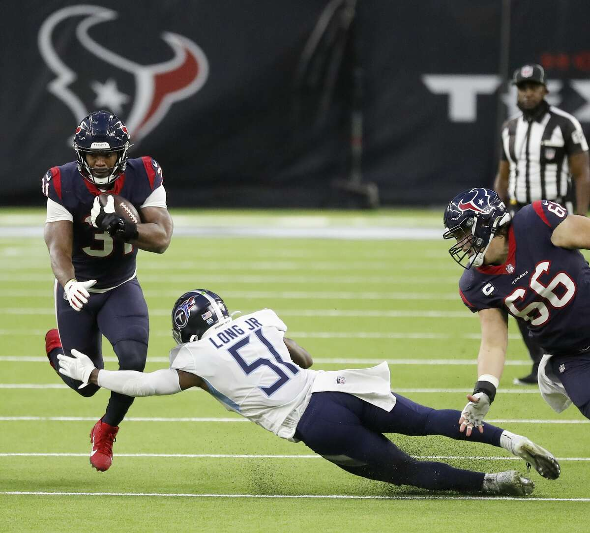 Houston Texans running back David Johnson (31) gains yardage as Tennessee Titans linebacker David Long (51) during the third quarter of an NFL football game Sunday, Jan. 3, 2021, at NRG Stadium in Houston .