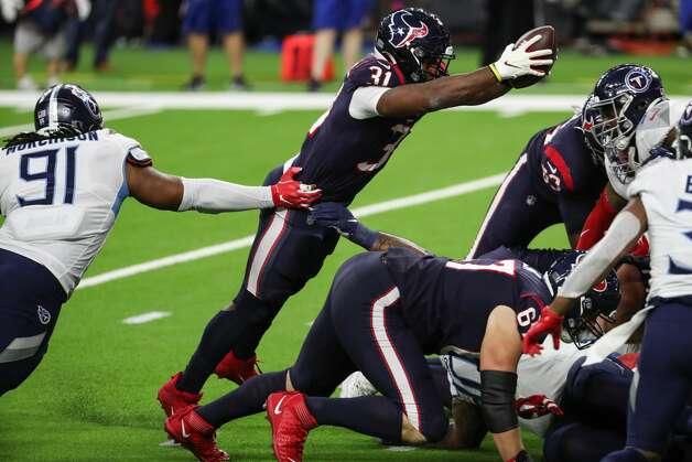 Houston Texans running back David Johnson (31) leaps over the line line past Tennessee Titans defensive tackle Larrell Murchison (91) for a 1-yard touchdown run during the third quarter of an NFL football game at NRG Stadium on Sunday, Jan. 3, 2021, in Houston. Photo: Brett Coomer/Staff Photographer / © 2021 Houston Chronicle