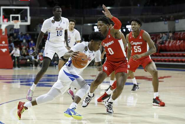 SMU guard Kendric Davis, front center, drives toward the basket while Houston guard Marcus Sasser (0) defends during the second half of an NCAA college basketball game in Dallas, Sunday, Jan. 3, 2021. (AP Photo/Roger Steinman) Photo: Roger Steinman/Associated Press / Copyright 2021 The Associated Press. All rights reserved.