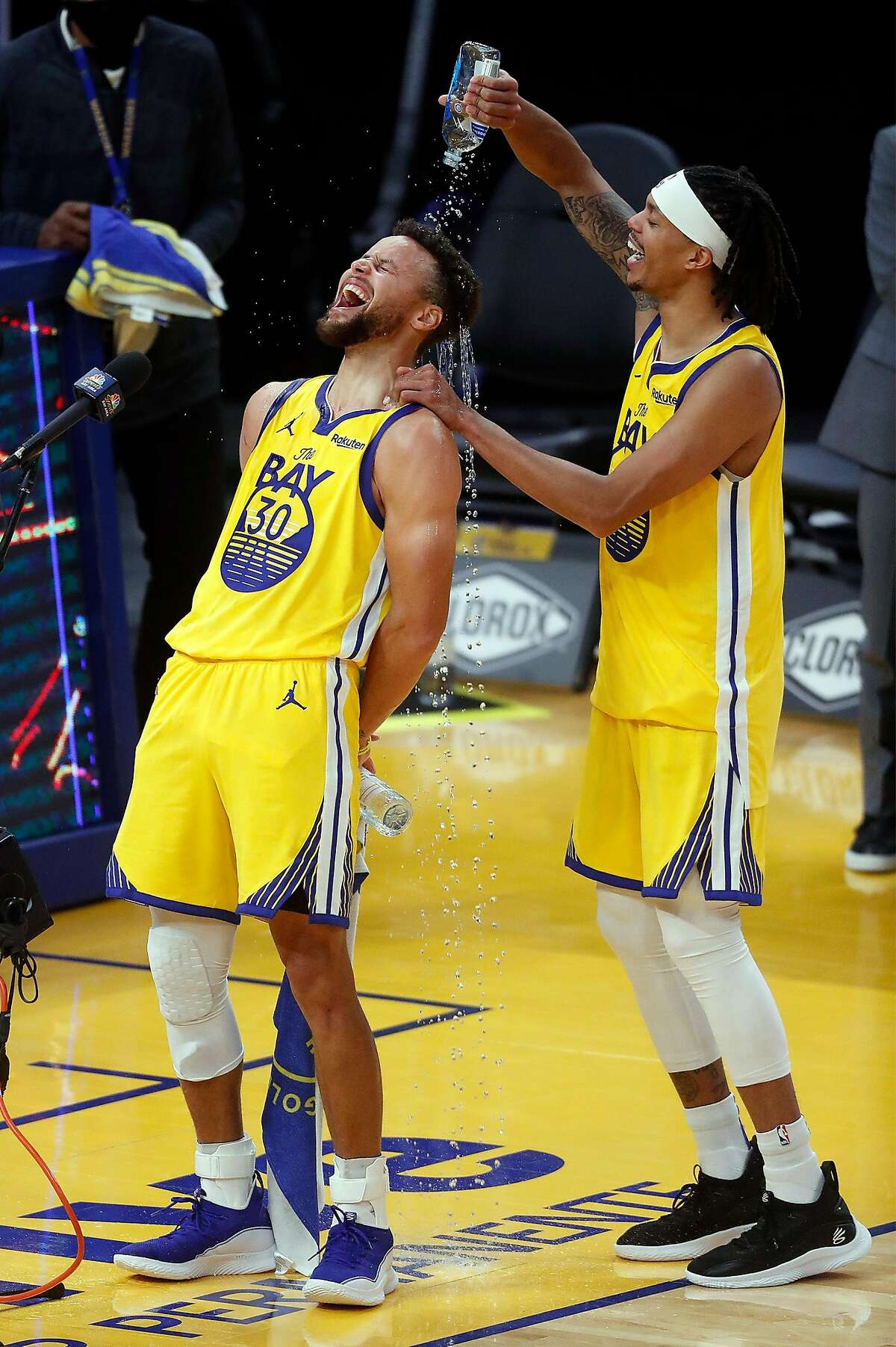 After scoring a career high 62 points, Golden State Warriors' Stephen Curry gets a bottle of water poured on him by Damion Lee after Warriors' 137-122 win over Portland Trail Blazers in NBA game at Chase Center in San Francisco, Calif., on Sunday, January 3, 2021.