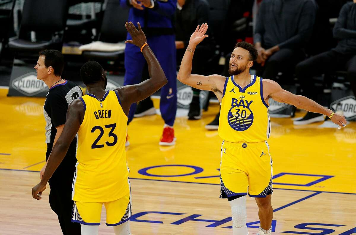 FILE: Stephen Curry of the Golden State Warriors celebrates with Draymond Green #23 after making his final three-point basket of the night to give him a career-high 62 points during their game against the Portland Trail Blazers at Chase Center on January 03, 2021 in San Francisco, California.