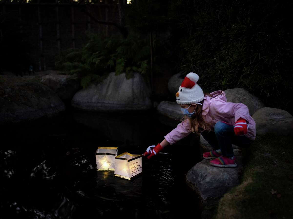 Scarlett Reed, 6, drops her lantern bearing a wish for the new year into the pond at the San Antonio Botanical Garden.