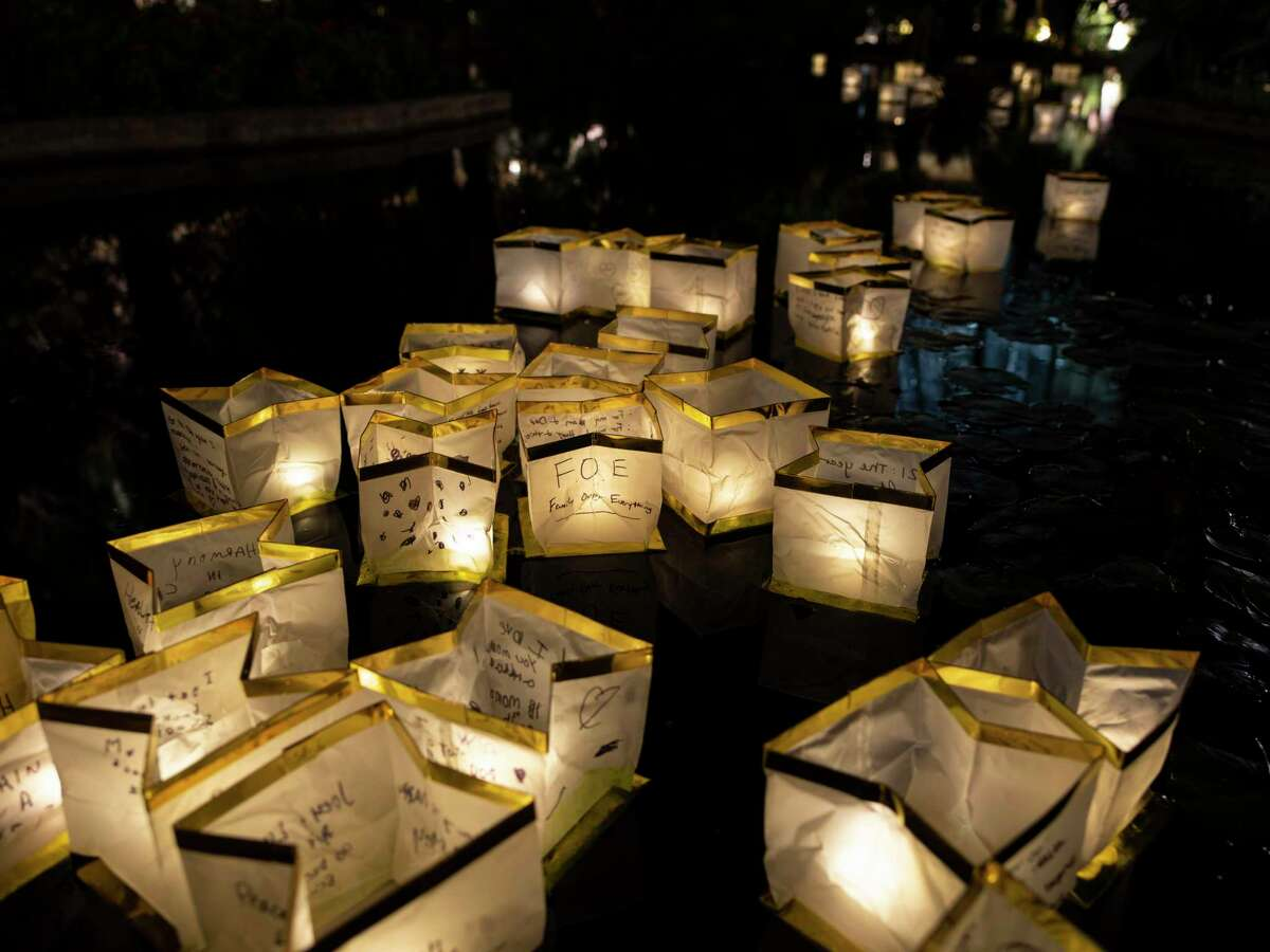 In Japanese tradition, the candle lights in white paper launched on water represent loved ones retuning to from where they came from.