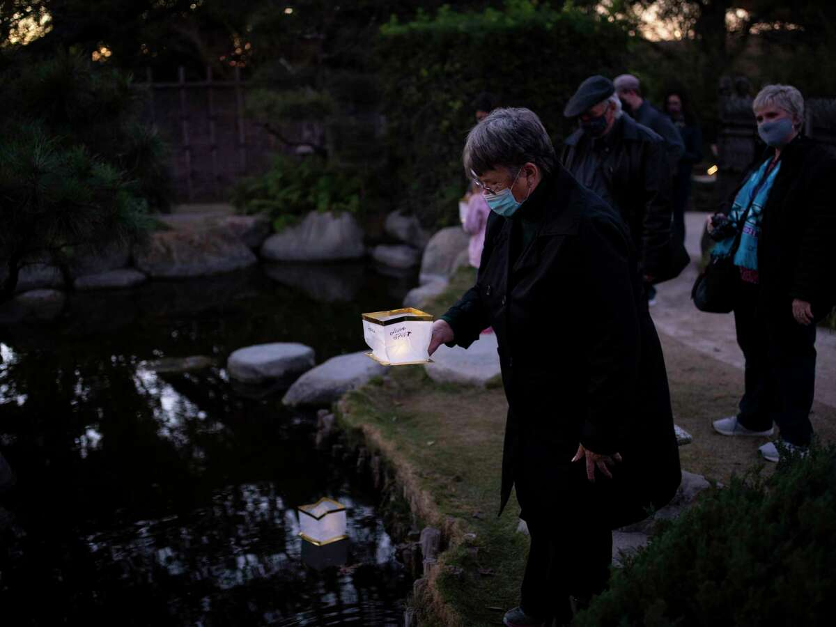 Attendees drop lanterns with their wishes for the year ahead into the ponds at the San Antonio Botanical Gardens in San Antonio, Tx., U.S., on Saturday, January 02, 2021.