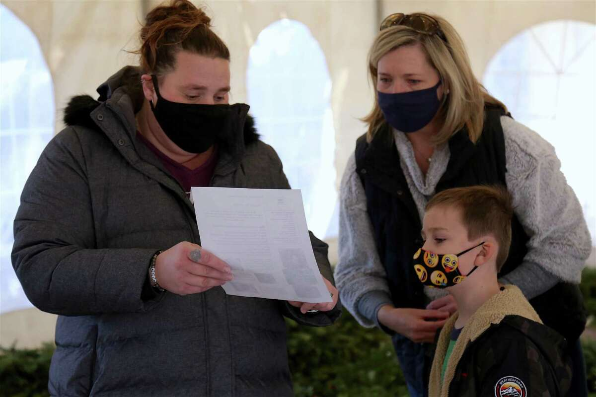 Jennifer Bradshaw, early childhood education coordinator, explains details to Laura Lynch of Wilton and her son Gavin, 6, at the Wreaths for Wildlife at the Woodcock Nature Center on Tuesday, Dec. 29, 2020.
