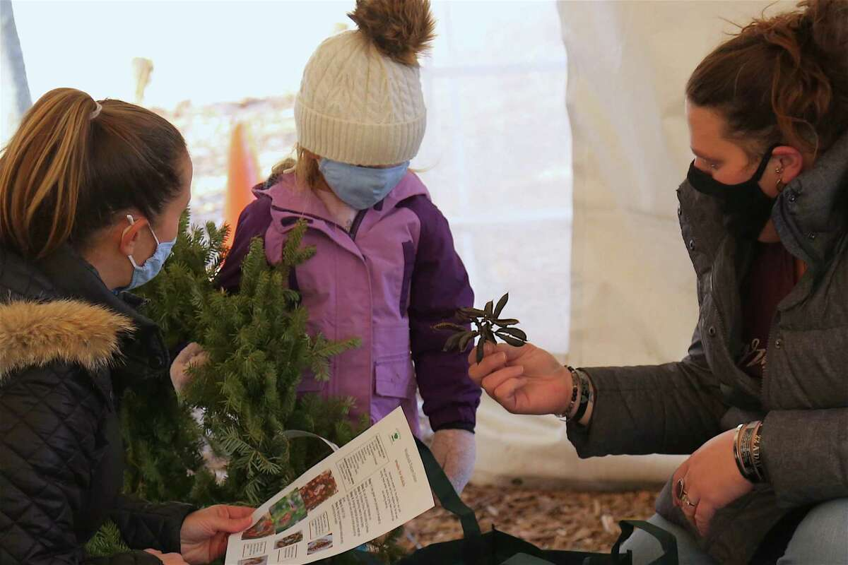 Jennifer Bradshaw, early childhood education coordinator, explains the contents of the kit to Amanda Duff of Ridgefield and her daughter Mac, 3, at the Wreaths for Wildlife at the Woodcock Nature Center on Tuesday, Dec. 29, 2020.