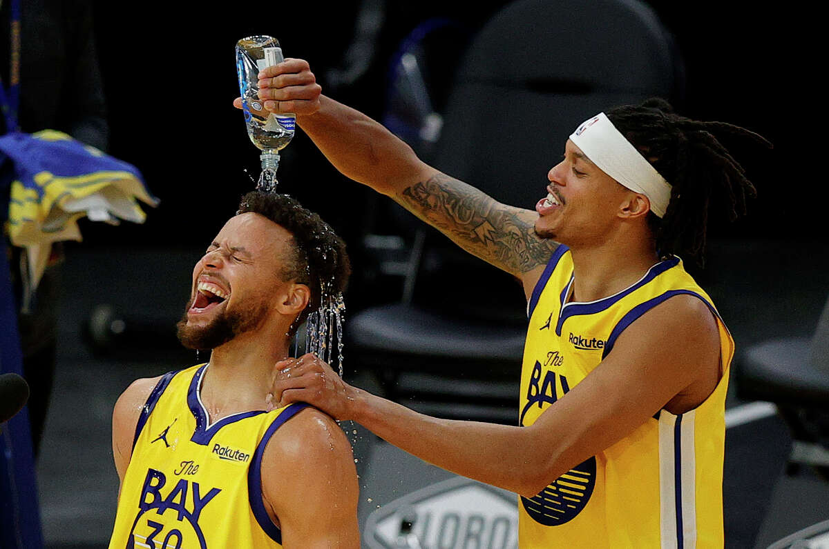 Stephen Curry of the Golden State Warriors is showered in water by Damion Lee during a post-game interview after Curry scored a career-high 62 points against the Portland Trail Blazers at Chase Center(Photo by Ezra Shaw/Getty Images)