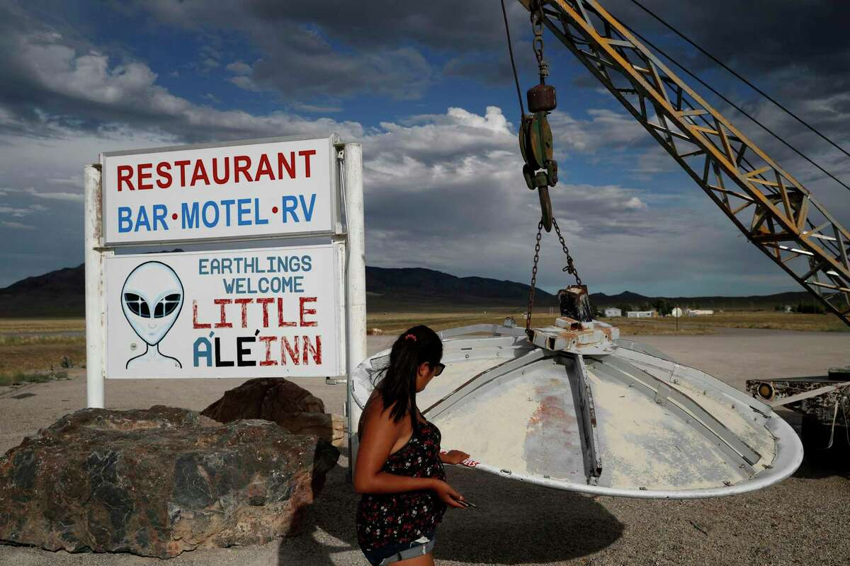 In this July 22, 2019 photo, Grace Capati looks at a UFO display outside of the Little A'Le'Inn, in Rachel, Nev., the closest town to Area 51. The U.S. Air Force has warned people against participating in an internet joke suggesting a large crowd of people
