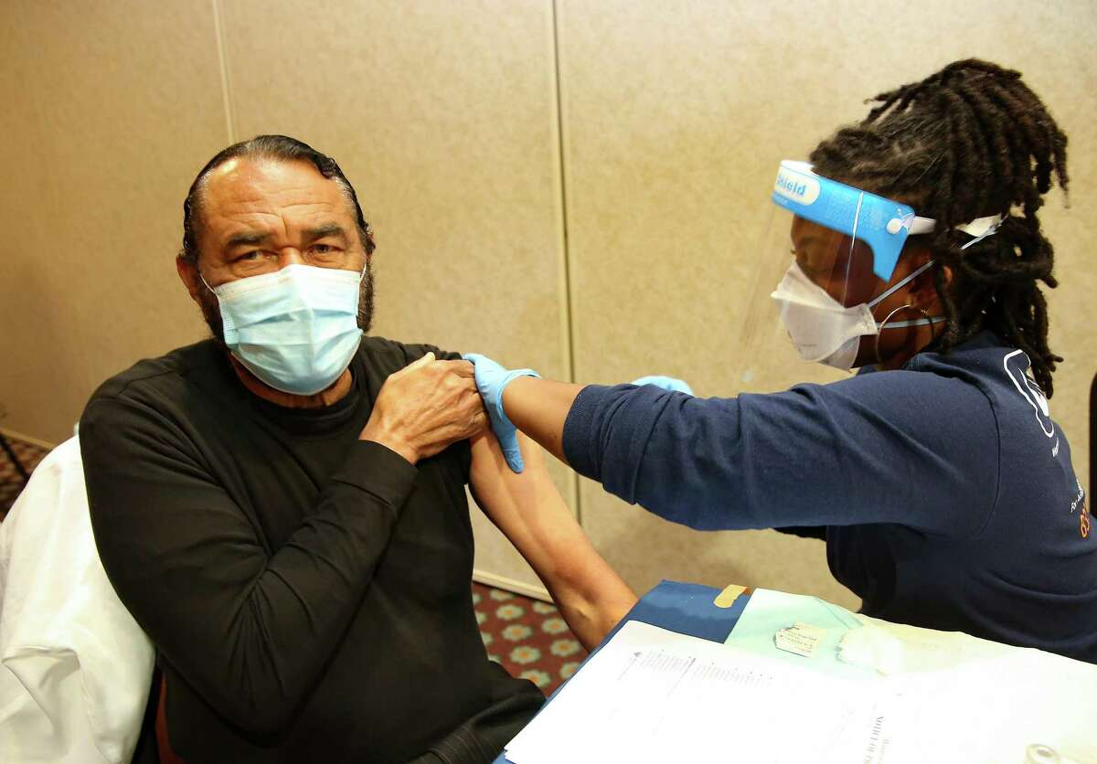 U.S. Rep. Al Green gets his COVID-19 vaccine shot by public health nurse Kerri Hurt as the Houston Health Dept., rolls out public vaccines at Bayou City Events Center in Houston on Saturday, Jan. 2, 2021.