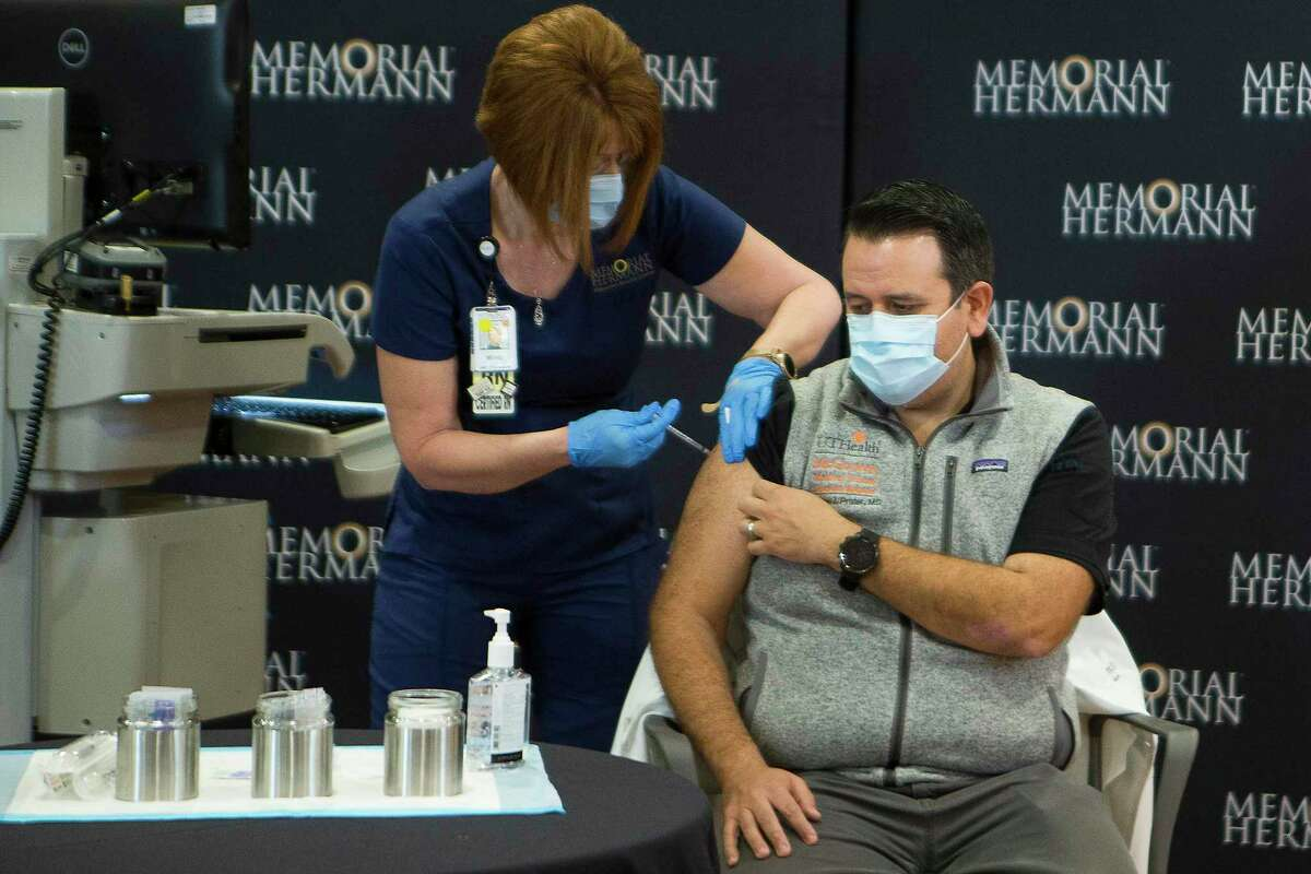 Dr. Sam Prater, UTHealth/Memorial Hermann Emergency Medicine physician, receives a dose of the Pfizer Covid-19 vaccination from Mindy Warren, at Memorial Hermann Hospital in the Texas Medical Center.