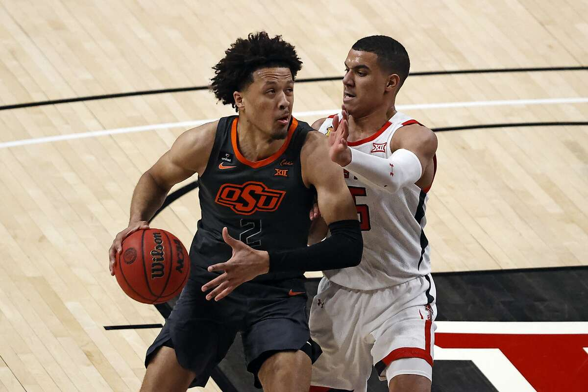 Oklahoma State's Cade Cunningham (2) dribbles around Texas Tech's Kevin McCullar (15) during the second half of an NCAA college basketball game Saturday, Jan. 2, 2021, in Lubbock, Texas. (AP Photo/Brad Tollefson)