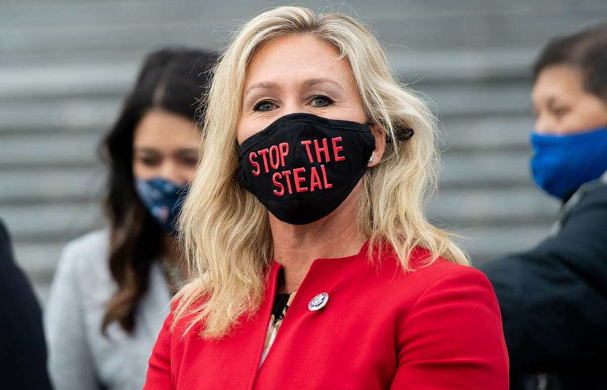 """U.S. Rep. Marjorie Taylor Greene, R-Ga., wears a """"Stop the Steal"""" mask while speaking with fellow first-term Republican members of Congress on the steps of the U.S. Capitol in Washington, D.C., Jan. 4, 2021."""