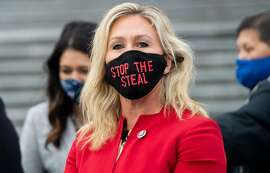 "US Representative Marjorie Taylor Greene, Republican of Georgia, holds up a ""Stop the Steal"" mask while speaking with fellow first-term Republican members of Congress on the steps of the US Capitol in Washington, DC, January 4, 2021. - Donald Trump and Joe Biden head to Georgia on Monday to rally their party faithful ahead of twin runoffs that will decide who controls the US Senate, one day after the release of a bombshell recording of the outgoing president that rocked Washington.If Democratic challengers defeat the Republican incumbents in both races Tuesday, the split in the upper chamber of Congress will be 50-50, meaning incoming Vice President Kamala Harris will have the deciding vote. (Photo by SAUL LOEB / AFP) (Photo by SAUL LOEB/AFP via Getty Images)"