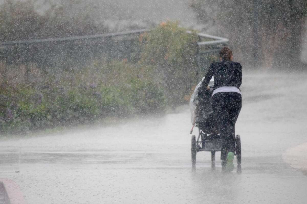 A woman jogs during a heavy rainfall along Lake Merritt in Oakland, California on Jan. 4, 2021. A cold front passing through the San Francisco Bay Area included high winds and brief periods of intense rainfall.