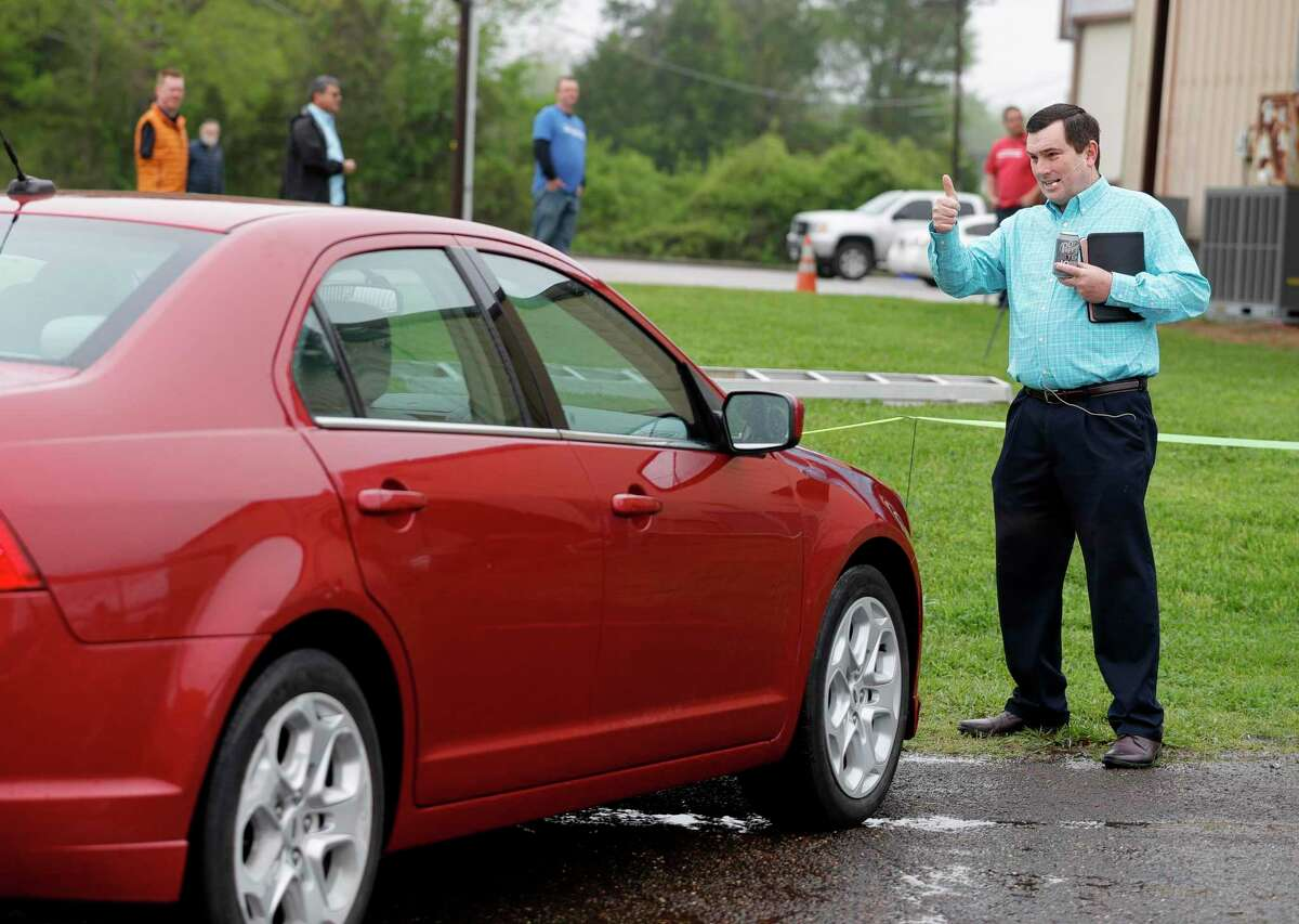 Pastor Chris Gober gives a thumbs-up after helping to direct a parishioner's car into place before a drive-in style service at First Montgomery Baptist Church on March 22 in Montgomery. More than 200 parishioners attended the service.