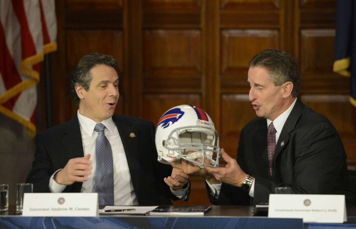 Governor Andrew Cuomo, left receives a Buffalo Bills helmet from former Lt. Governor Robert Duffy in 2013. Cuomo recently decided to allow fans to attend an upcoming Bills playoff game. (Times Union archive)