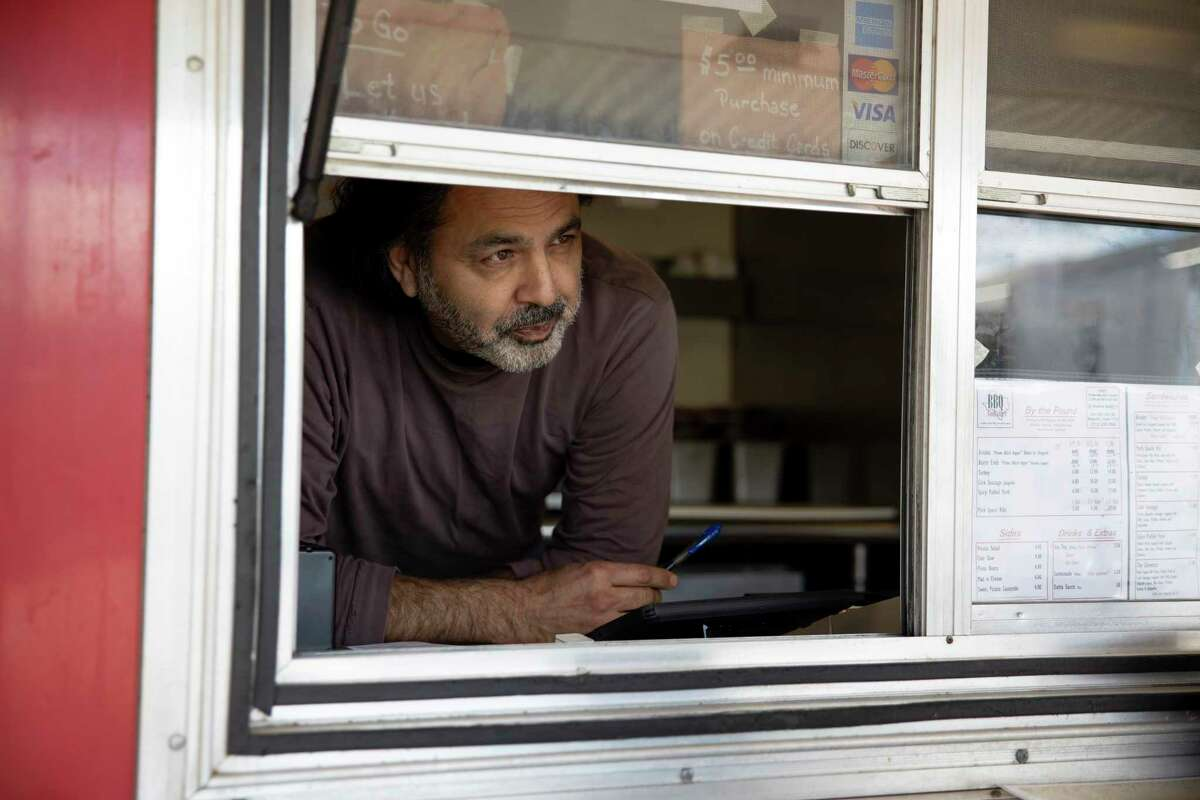 Tony Faour, owners of BBQ Godfather peeks through his order window at Deacon Baldy's Bar & Food Trucks, Thursday, Oct. 30, 2020, in Magnolia. Faour was forced to shut down due to closures from the COVID-19 pandemic but states he's been successful after reopening.