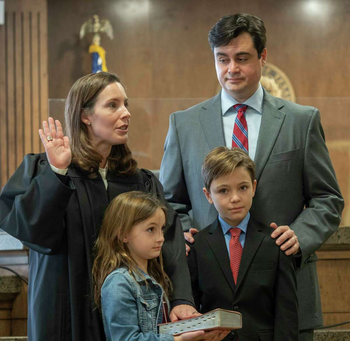 Judge Jeff Robnett gives the oath of office to Judge Leah Robertson, with her husband Stephen and children Ethan and Emma 01/04/2021 in the Midland County 142nd District Courtroom. Tim Fischer/Reporter-Telegram