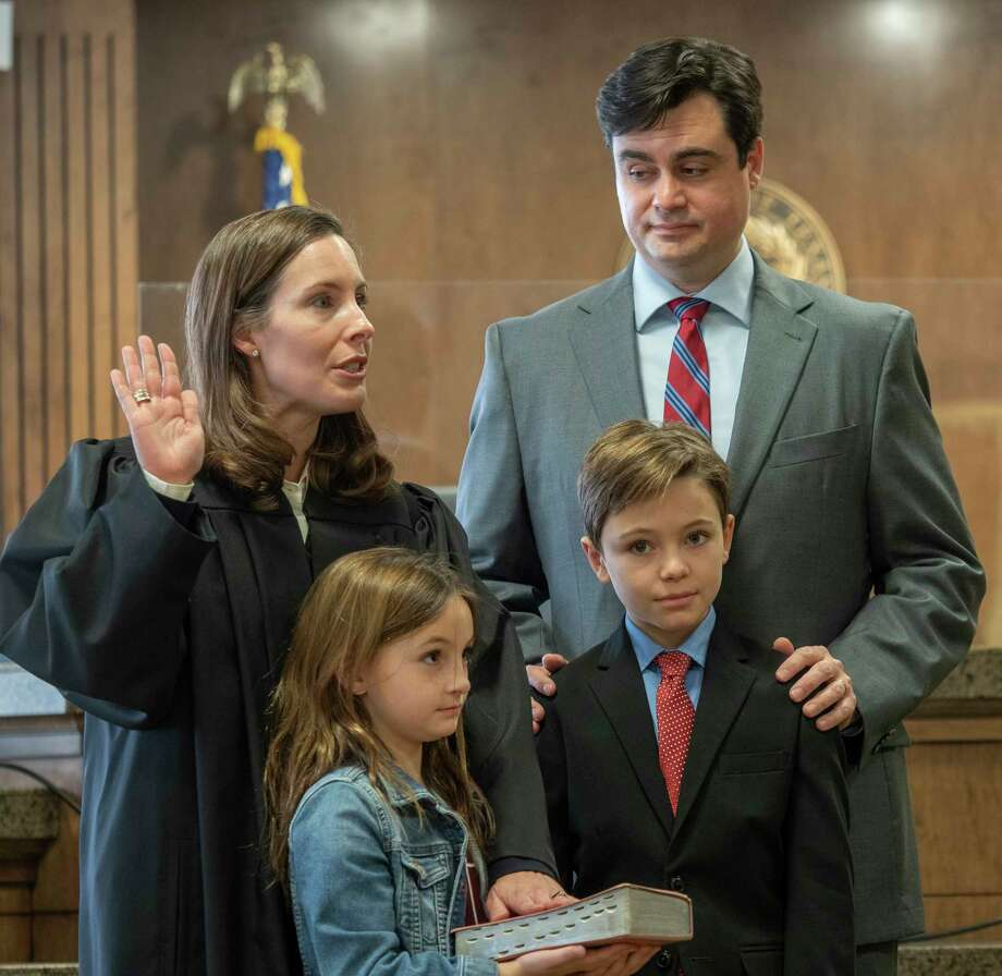 Judge Jeff Robnett gives the oath of office to Judge Leah Robertson, with her husband Stephen and children Ethan and Emma 01/04/2021 in the Midland County 142nd District Courtroom. Tim Fischer/Reporter-Telegram Photo: Tim Fischer, Midland Reporter-Telegram
