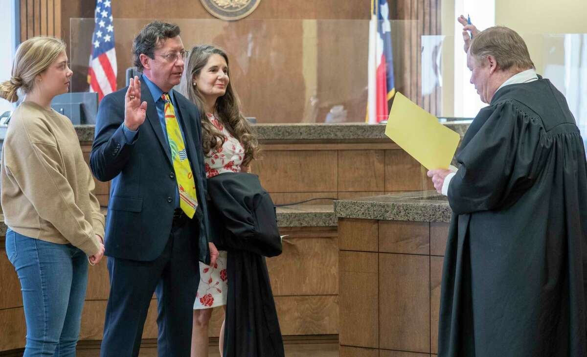 Judge Jeff Robnett gives the oath of office to Judge David Rogers, taking over the 142nd District Court, with his wife Michele and daughter Elle 01/04/2021 in the Midland County 142nd District Courtroom. Tim Fischer/Reporter-Telegram