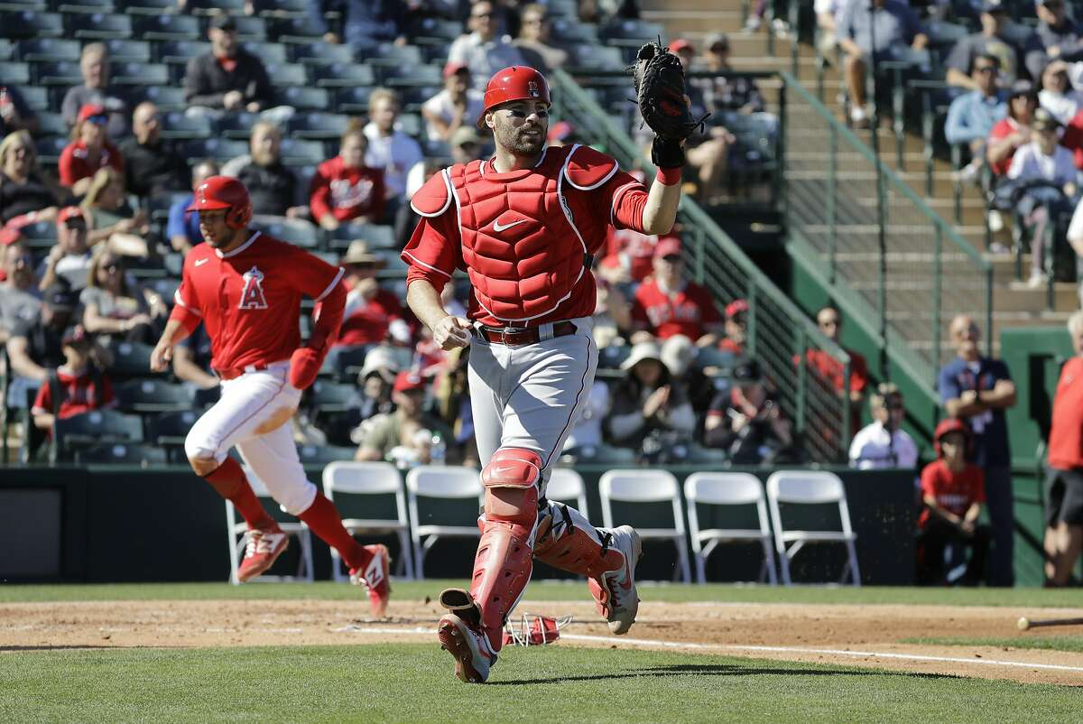 Cincinnati Reds' Curt Casali catches a throws as Los Angeles Angels' David Fletcher scores during the second inning of a spring training baseball game, Tuesday, Feb. 25, 2020, in Tempe, Ariz. (AP Photo/Darron Cummings)