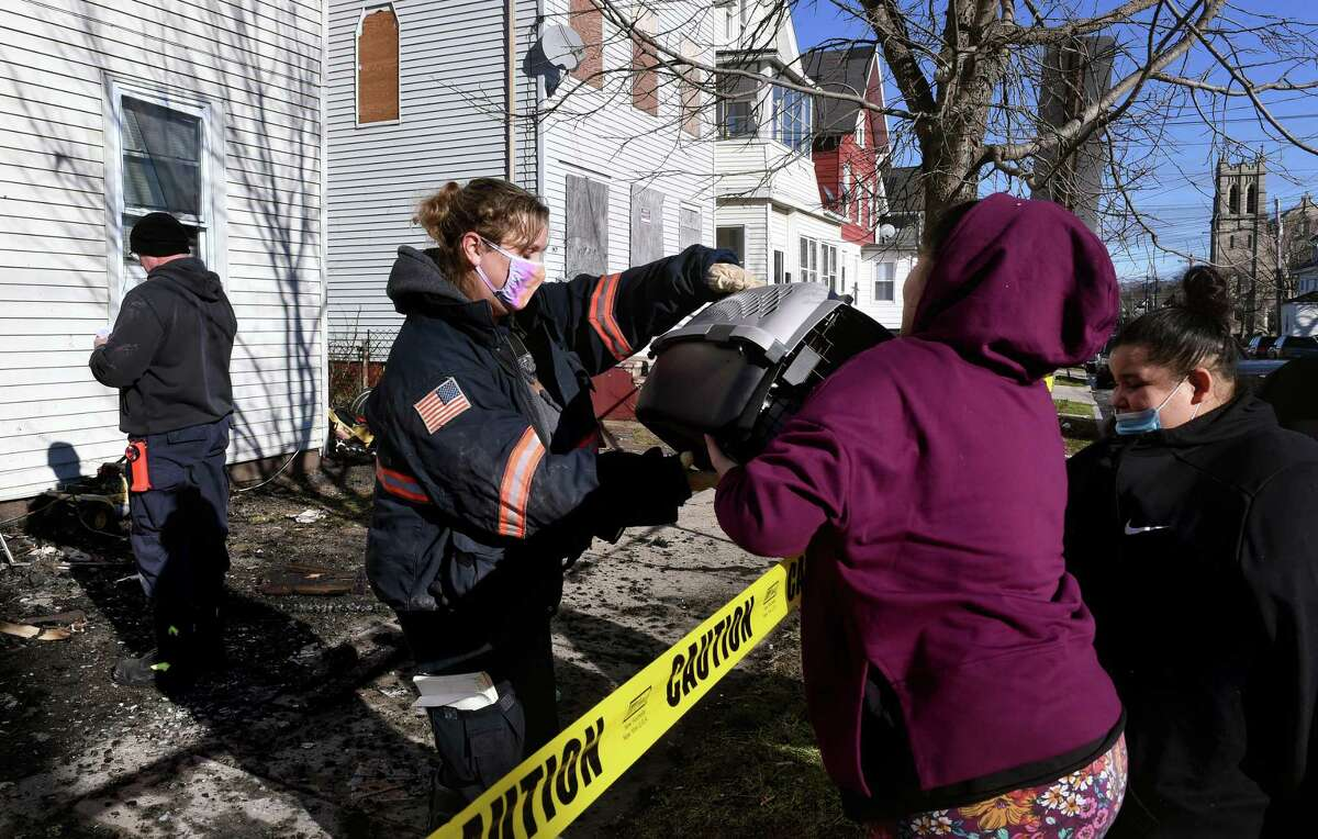 State Fire Investigation Unit Detective Laura Kraus, left, hands a pet carrier with a family's cat, Moo Moo, to Yazmine Ruiz, right, 13, and her mother, Vanessa Torres, far right, that she retrieved from a multi-unit home at 151 Saltonstall Avenue in New Haven on January 4, 2021 following a fire in the early morning hours.