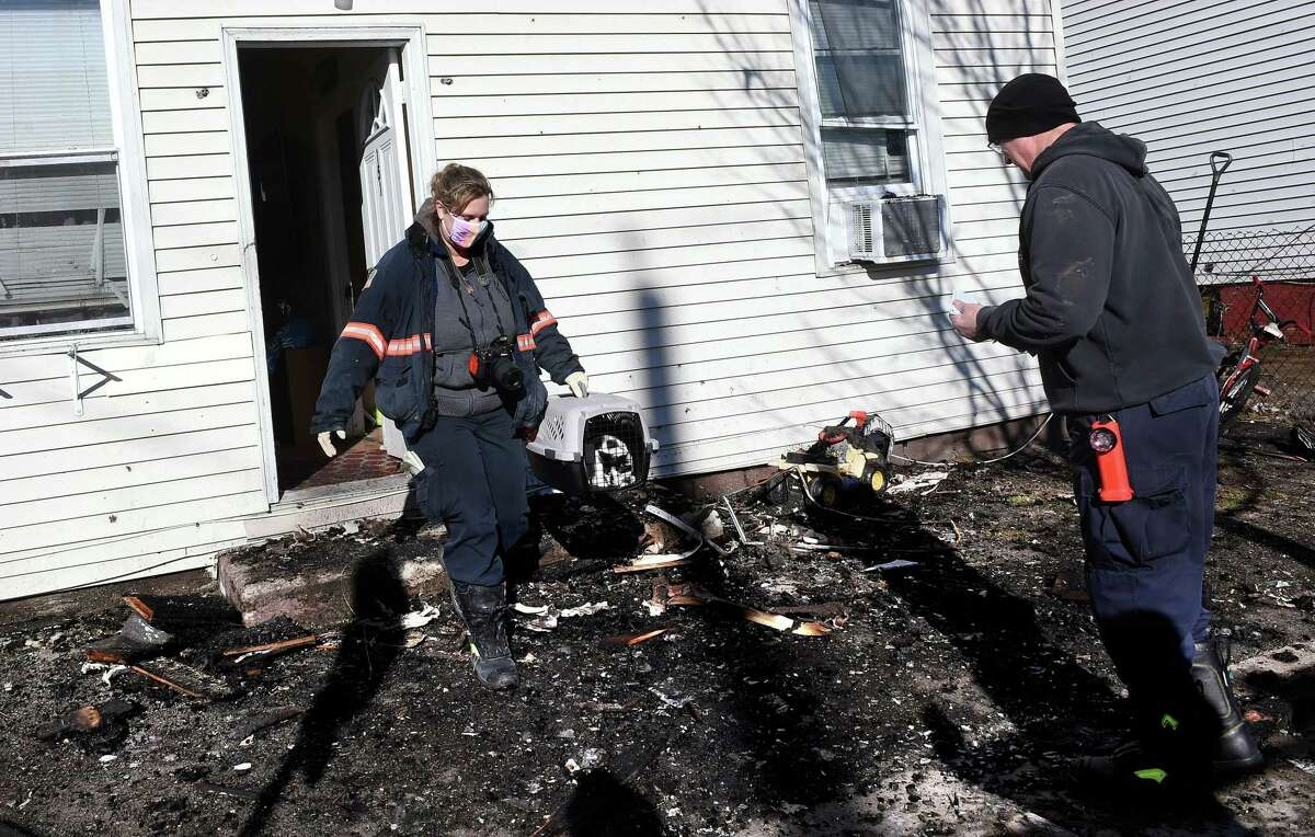 State Fire Investigation Unit Detective Laura Kraus (left) brings out a family's cat, Moo Moo, that she retrieved from a multi-unit home at 151 Saltonstall Avenue in New Haven on January 4, 2021 following a fire in the early morning hours.