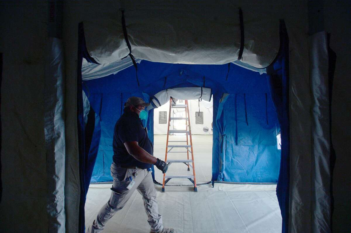 A crew with the Emergency Management Department erect a 96 x 20 foot triage tent outside the Emergency Room at Baptist Hospital in Beaumont Monday. The tent will alleviate wait times for non-acute, non-COVID-19 patients seeking treatment at the ER. The tents will have all necessary equipment and can hold 12 beds. Staff expect the unit to be up and running Tuesday morning. Photo taken Monday, January 4, 2021 Kim Brent/The Enterprise