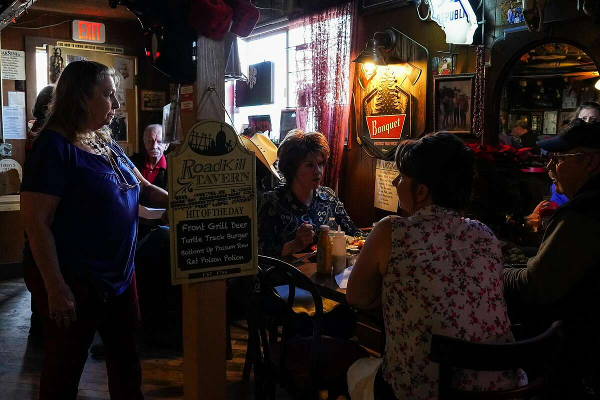Robbie Nelson talks with customers inside her Airport Bar & Grill in Mariposa, Calif. Many local residents arrived for lunch and drinks in support of Nelson's defiance of COVID-19 regulations. Very few wore masks.