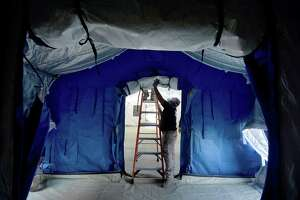 A crew with the Emergency Management Department, including Moses Vasquez, erect a 96 x 20 foot triage tent outside the Emergency Room at Baptist Hospital in Beaumont Monday. The tent will alleviate wait times for non-acute, non-COVID-19 patients seeking treatment at the ER. The tents will have all necessary equipment and can hold 12 beds. Staff expect the unit to be up and running Tuesday morning. Photo taken Monday, January 4, 2021 Kim Brent/The Enterprise