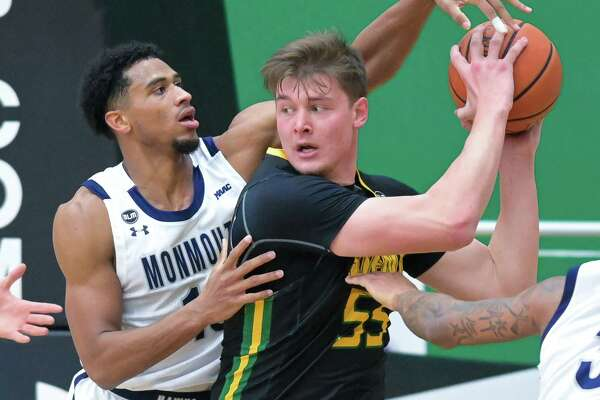 Monmouth University senior Marcus McClary gets a hand on the ball held by Siena senior Jackson Stormo during a Metro Atlantic Athletic Conference game at the Siena College Alumni Recreation Center in Loudonville, NY, on Monday, Jan. 4, 2020 (Jim Franco/special to the Times Union.)