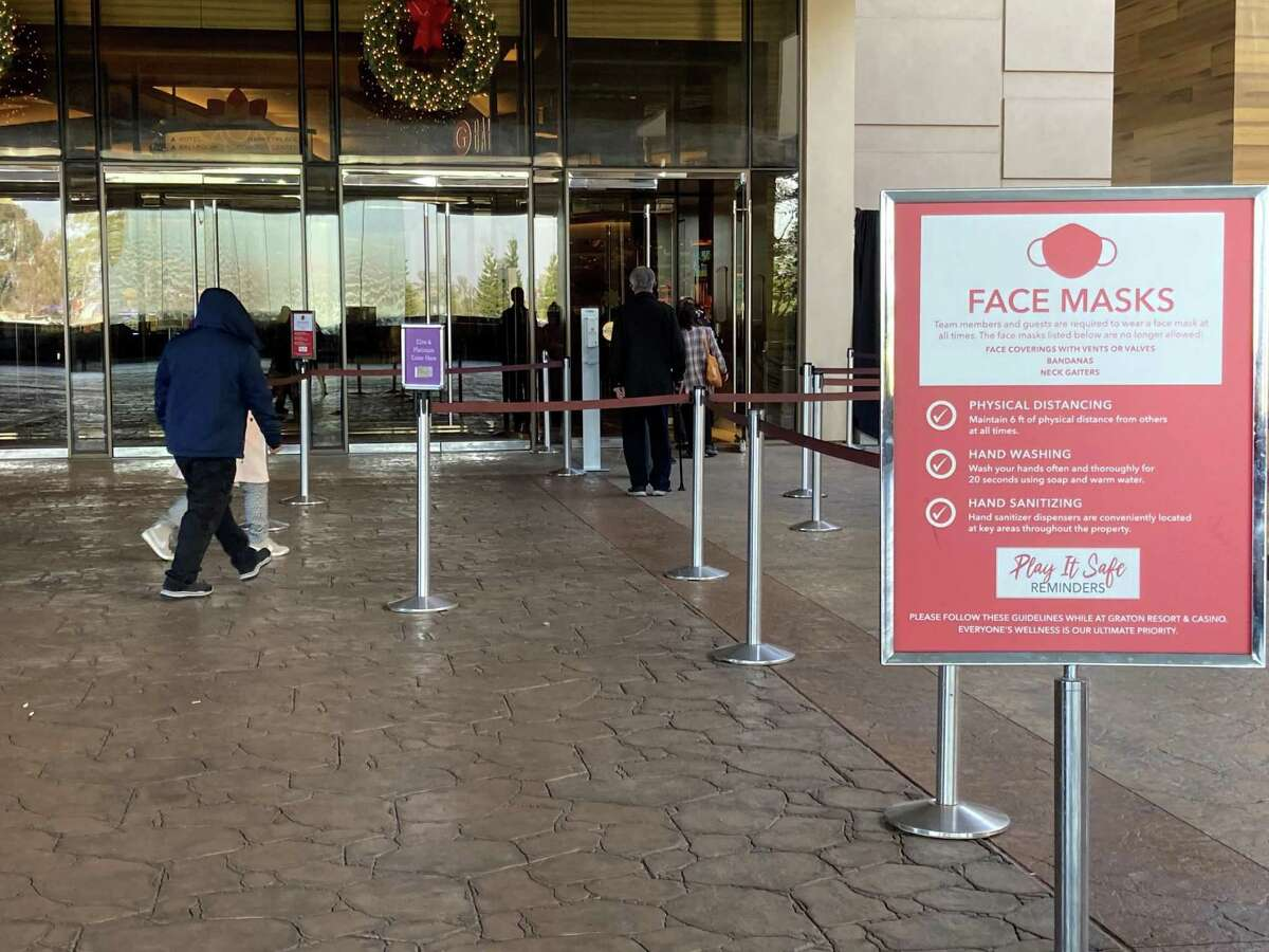 Gamblers from a chartered bus head into the Graton Resort and Casino in December, lining up for temperature checks outside the entrance.