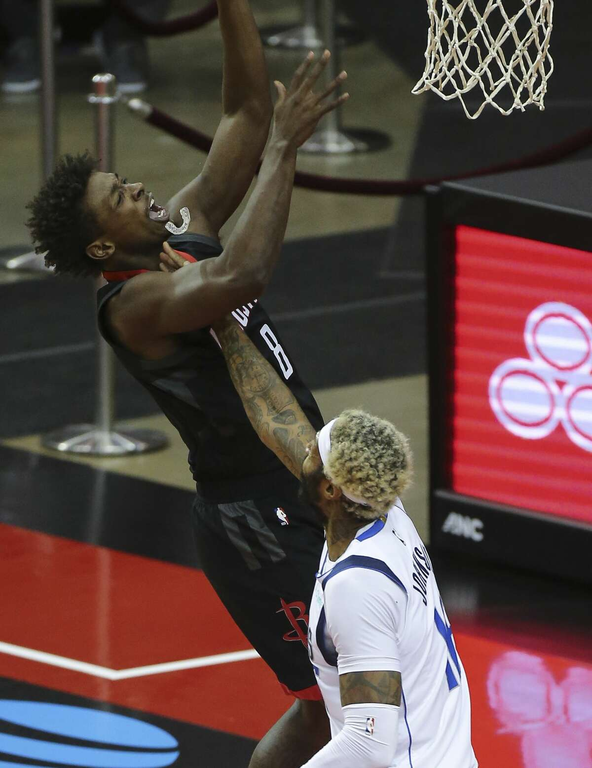 Houston Rockets forward Jae'Sean Tate's (8) mouth guard comes off when he is fouled by Dallas Mavericks forward James Johnson (16) during the third quarter of a NBA game Monday, Jan. 4, 2021, at Toyota Center in Houston.